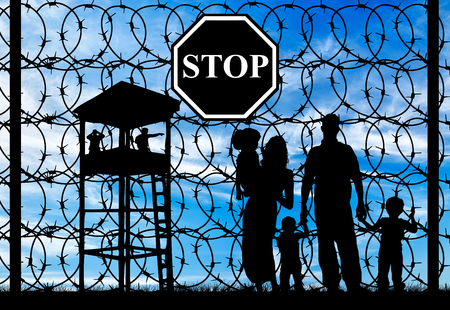 barbed wire fence: Concept of refugee. Silhouette of a family with children of refugees and fence with barbed wire and watch tower Stock Photo