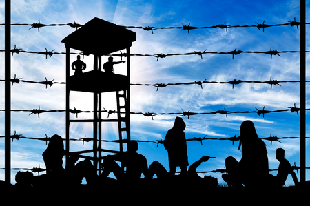 middle east crisis: Concept of refugee. Silhouette of a crowd of refugees rest on the ground near the fence or barbed wire and watchtower Stock Photo