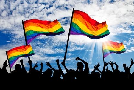 lesbianas: Silueta de un desfile de gays y lesbianas con una bandera del arco iris Foto de archivo