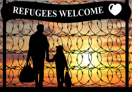 illegals: Concept of refugee. Silhouette of a family with a child refugee father near the fence with barbed wire and the inscription welcome refugees Stock Photo