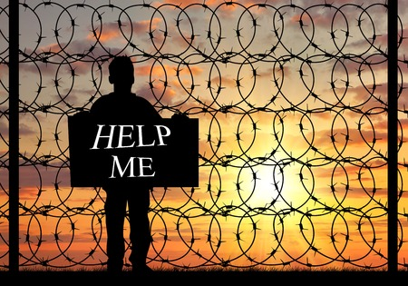 illegals: Concept of refugee. Silhouette of a refugee with a poster asking for help against the sunset