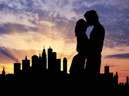 oncept: ?oncept of a date. Silhouette of a young couple kissing on the background of evening city Stock Photo