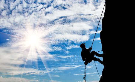 purposeful: The concept of perseverance. Silhouette climber steadily climb the mountain Stock Photo