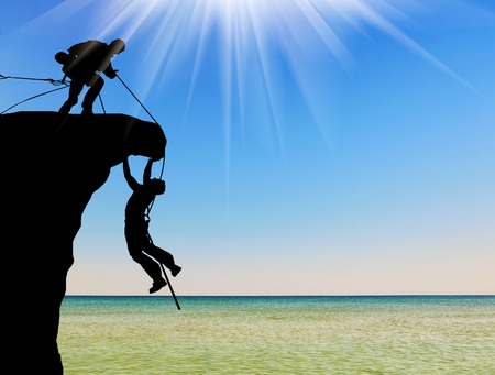 the help: Concept of aid. Silhouette of two climbers help each other Stock Photo