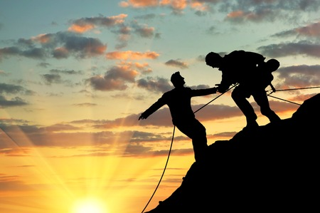 Concept of aid. Silhouette of two climbers help each other Imagens