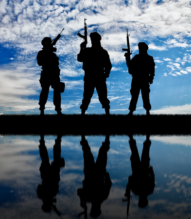 corpses: Concept of a terrorist. Silhouette of terrorists with a rifle and a reflection on the water against the background of dawn