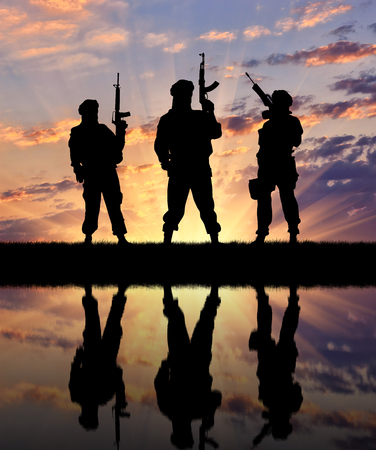 terrorists: Concept of a terrorist. Silhouette of terrorists with a rifle and a reflection on the water at sunset