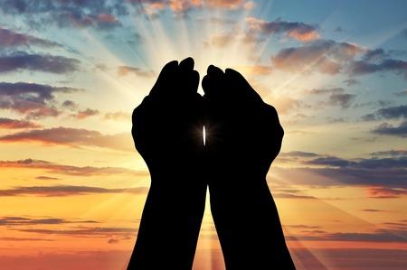 ? イスラム教、コーランの概念。夕暮れ空に直面して手を祈ってのシルエット