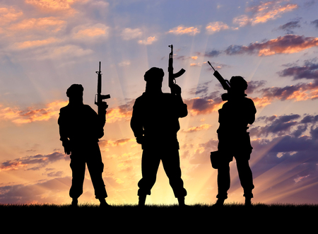 conflict: Concept of a terrorist. Silhouette terrorists with rifle at sunset