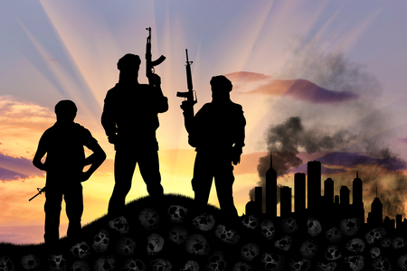 iraq war: Concept of a terrorist attack. Silhouette of terrorists with a rifle standing on a pile of skulls on the background of the city in smoke