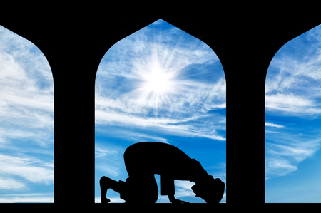 islamic prayer: The concept of the Islamic religion. Silhouette of man praying at the Town Hall