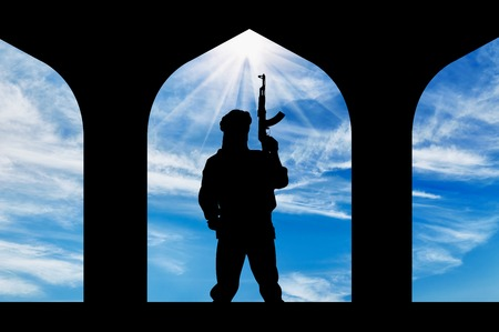 Concept of terrorism. Silhouette of a terrorist with a gun in a building Stock Photo