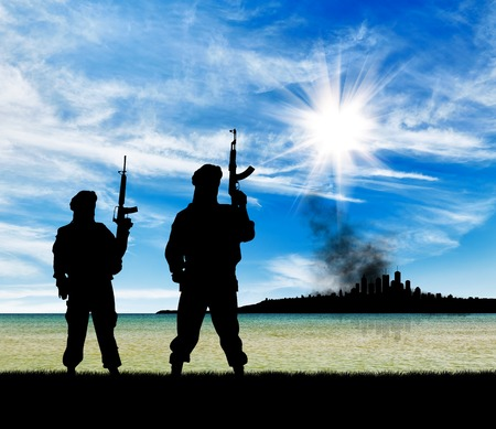 terrorists: Concept of a terrorist attack. Silhouette of terrorists with a rifle on a background of the city in smoke