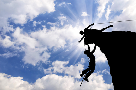 partnership power: Concept of aid. Silhouette of two climbers help each other Stock Photo