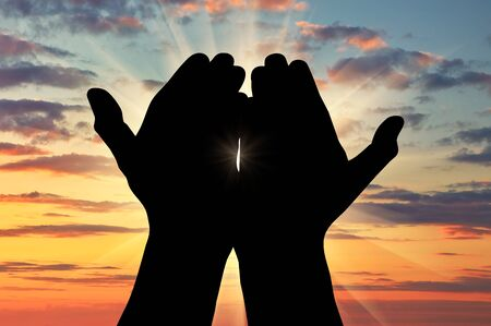 manos orando: ? oncept del Islam, el Corán. Silueta de rezar las manos hacia el cielo al atardecer