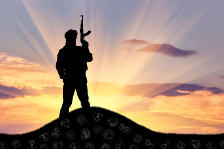 groupings: Concept of terrorism. Silhouette of a terrorist with a rifle standing on a pile of skulls at sunset