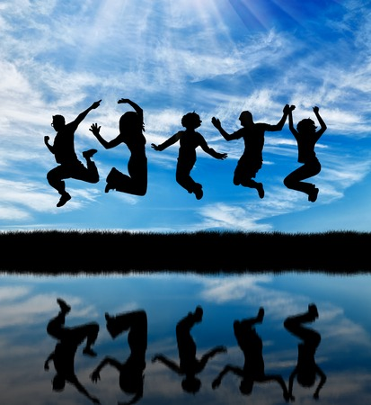 Concept of emotion. Silhouette of a happy group of people jumping against the sky