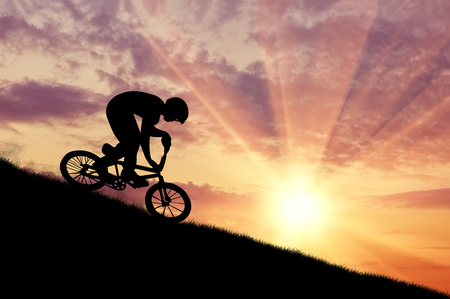 extreme sports: Concept of extreme sports. Silhouette of a cyclist moving at sunset Stock Photo