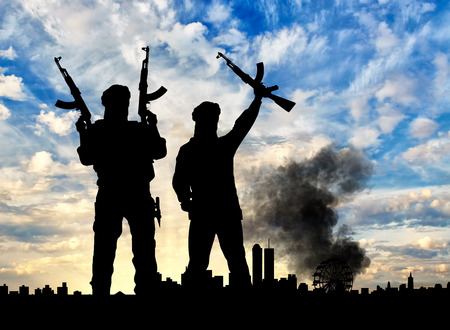 corpses: Concept of terrorism. Silhouette of the terrorists and the city in smoke against the sunset