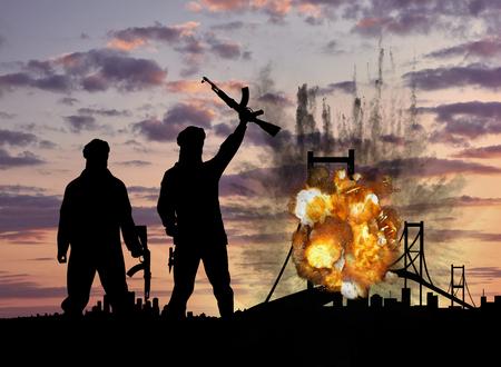 テロとテロ行為の概念。日没で橋を爆破しテロリストのシルエット