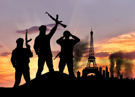 terrorists: Concept of terrorism. Silhouette of the terrorists and the city in smoke against the sunset