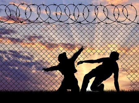 illegals: Concept of the refugees. Silhouette of refugees crossed the border illegally through the hole in the fence Stock Photo