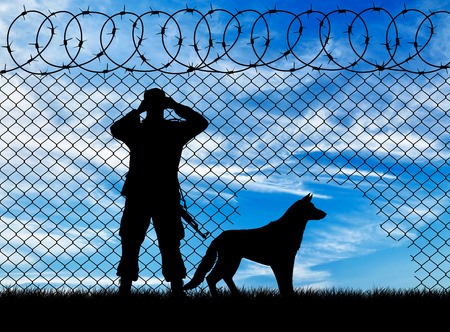 Concept of the refugees. Silhouette of a border guard and a dog near the hole in the fence Imagens