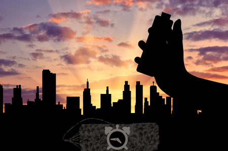 detonator: Concept of terrorism. Silhouette of a bomb with a detonator in his hand against the evening city Stock Photo