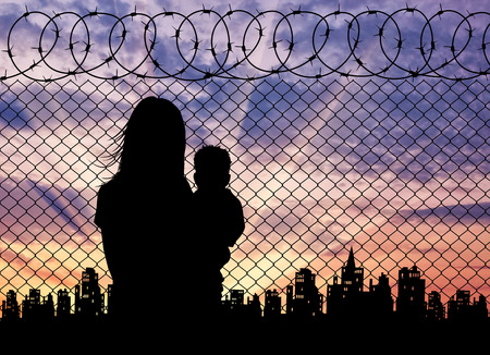 illegals: Concept of the refugees. Silhouette refugee mother with a baby in the background of the fence and the city at sunset Stock Photo