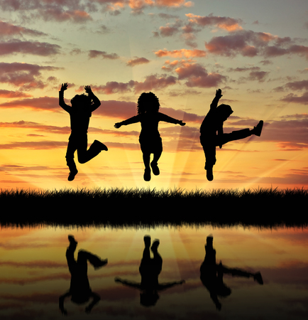 oncept: ?oncept of happiness. Silhouette happy children jumping at sunset and reflection in water Stock Photo