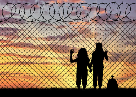 hungry children: Concept of the refugees. Silhouette of hungry children in desperate refugees near the fence at sunset Stock Photo