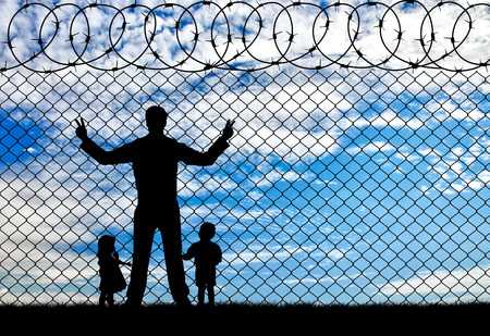 illegals: Concept of the refugees. Silhouette refugees father and two hungry children on the background of the fence
