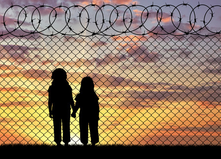 middle east crisis: Concept of the refugees. Silhouette of hungry children in desperate refugees near the fence at sunset Stock Photo
