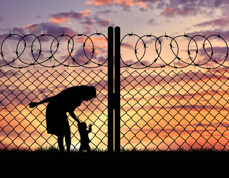 illegals: Concept of the refugees. Silhouette mother with child refugees near the fence at sunset