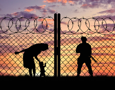 illegals: Concept of the refugees. Silhouette refugee mother with a baby and a border guard at sunset