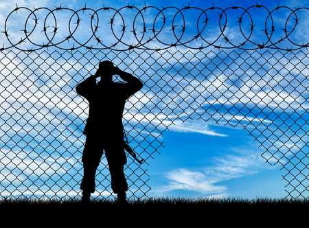power rangers: Concept of the refugees. Silhouette border guards near the hole in the fence Stock Photo