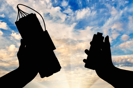 detonator: Concept of terrorism. Silhouette of a bomb with a detonator in his hands against the sky Stock Photo