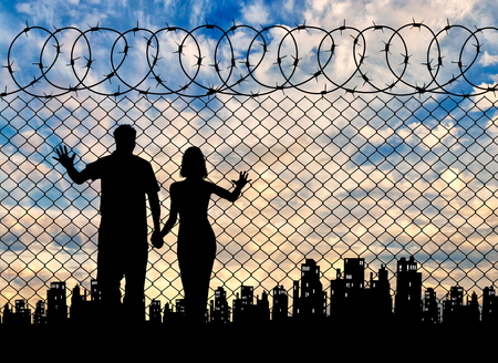 illegals: Concept of the refugees. Silhouette of refugee families near the fence on the background of the city and sunset