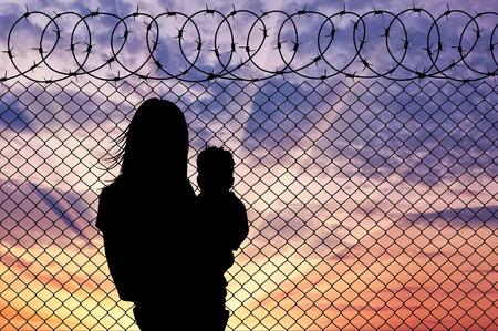難民の概念。日没でフェンスの近く子難民とシルエットの母