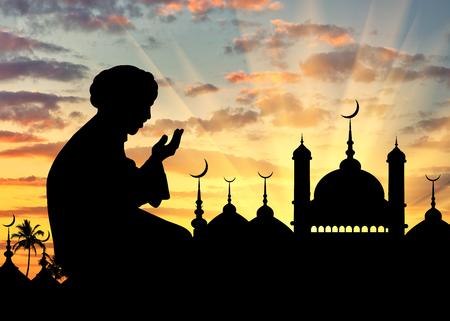 イスラムの宗教の概念。夕暮れ時の市庁舎の背景に祈って男のシルエット