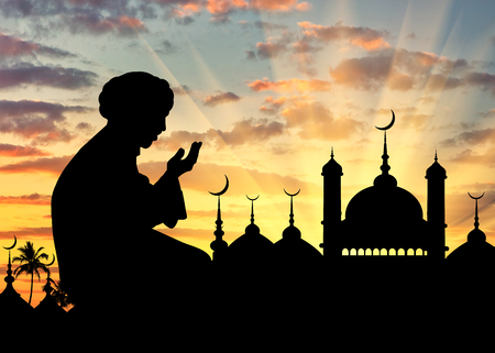 Concept of the Islamic religion. Silhouette of man praying on the background of the town hall at sunset