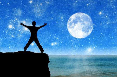 luz de luna: El concepto de éxito. Silueta de un hombre feliz en la cima de la montaña en el fondo del mar en la noche de luna