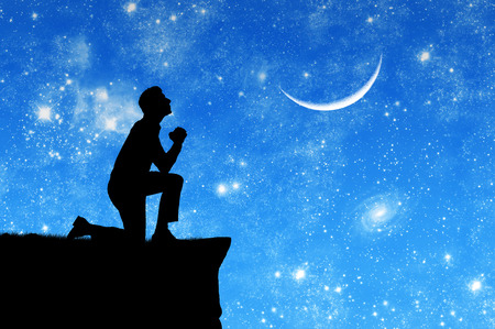 knelt: Concept of religion. Silhouette of man praying on the background of the sky with the moon and stars Stock Photo