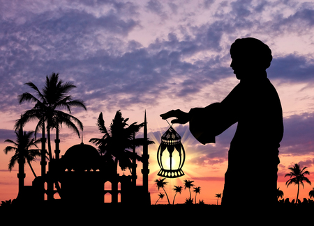 pious: ?oncept of Islamic culture. Silhouette of a man with a lamp in his hand against the sunset Stock Photo