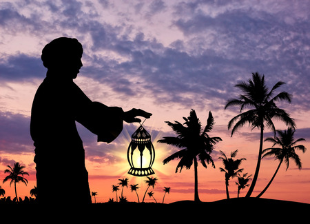 oncept: ?oncept of Islamic culture. Silhouette of a man with a lamp in his hand against the sunset Stock Photo