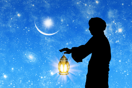 oncept: ?oncept of Islamic culture. Silhouette of a man with a lamp in his hand against the background of the starry sky and the moon
