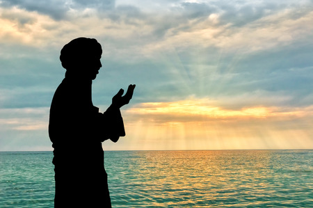 pious: Concept of Islamic culture. Silhouette of man praying on the background of the sea and a beautiful sunset Stock Photo