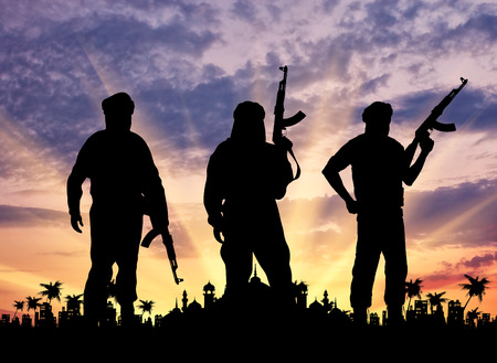 three palm trees: Concept of terrorism. Silhouette of three terrorists with weapons against the sunset and the town hall with palm trees