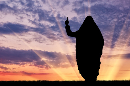dictate: Concept of terrorism. Silhouette of a terrorist dictate their terms and conditions at sunset