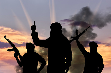 dictate: Concept of terrorism. Silhouette of three terrorists with weapons dictate their terms at sunset